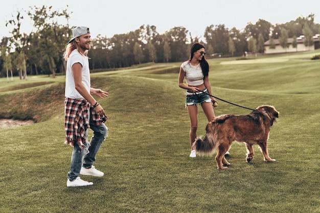 Hij is meer dan alleen een huisdier. volledige lengte van een mooi jong stel dat met hun hond speelt terwijl ze buiten zijn