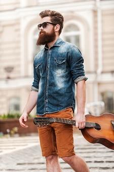 Hij is nooit ver van zijn gitaar. lage hoekmening van jonge, bebaarde man die gitaar vasthoudt en wegkijkt terwijl hij buiten loopt