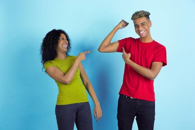 Hij is sterk, ze lacht. jonge emotionele afro-amerikaanse mooie man en vrouw in kleurrijke kleding op blauwe achtergrond. concept van menselijke emoties, gezichtsuitdrukking, relaties, advertentie, vriendschap.