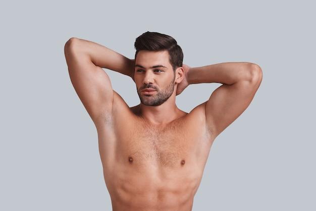 Hij kreeg een perfecte torso. knappe jonge man die handen achter het hoofd houdt en wegkijkt terwijl hij tegen een grijze achtergrond staat