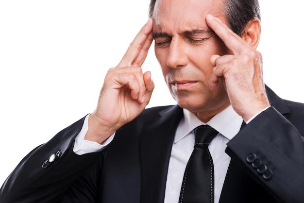Hij kreeg een stressvolle baan. gefrustreerde volwassen man in formele kleding die het hoofd met de vingers aanraakt en de ogen gesloten houdt terwijl hij tegen een grijze achtergrond staat