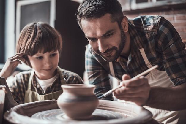 Hij leert graag nieuwe vaardigheden. kleine jongen die naar een zelfverzekerde jongeman kijkt die op een keramische pot trekt bij de pottenbakkersles