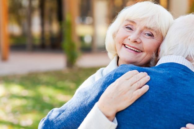 Hij maakt me blij. gelukkige oudere vrouw die haar man omhelst en glimlacht terwijl ze allebei buiten staan