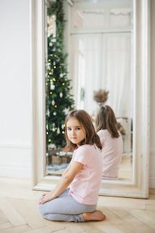 Hij meisje zit in de buurt van de spiegel, de spiegel reflecteert de kerstboom en lichten, het interieur is versierd, kerstmis, wachtend op de vakantie