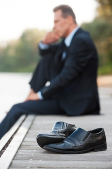 Hij moet nu alleen blijven. zijaanzicht van een doordachte zakenman die de hand op de kin houdt en wegkijkt terwijl hij op blote voeten aan de kade zit en met schoenen op de voorgrond