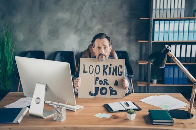 Hij ontsloeg humeurige ellendige agent makelaar makelaar man ex bedrijf eigenaar in handen promo plakkaat kijken baan economie wet advocaat op zolder industriële werkplek werkstation