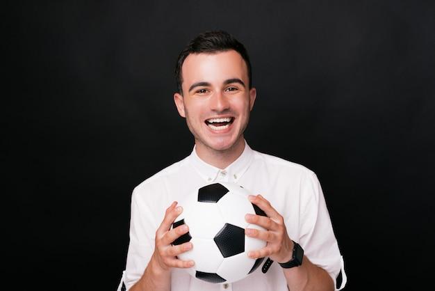 Hij ving de bal! doel!!! jonge opgewekte mens die een voetbalbal houden bekijkend de camera dicht tegen.
