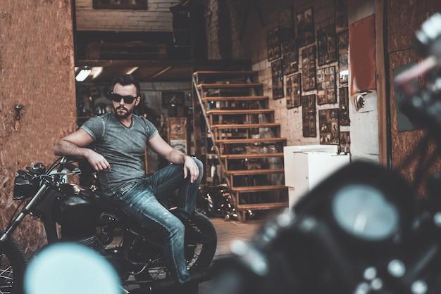 Hij weet alles van fietsen. knappe jonge man zittend op zijn fiets met motorgarage op de achtergrond