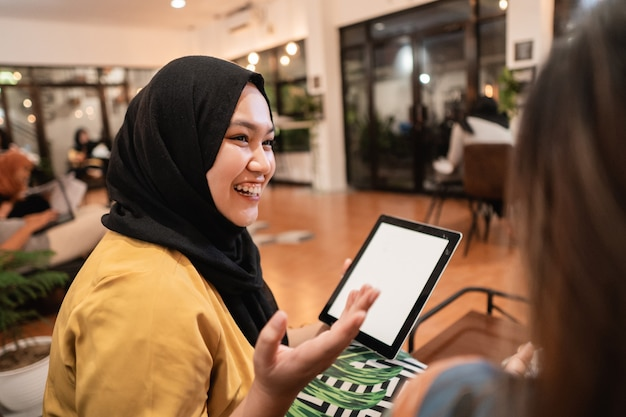 Hijab-meisje met behulp van tablet wanneer u geniet van samen chatten in de coffeeshop