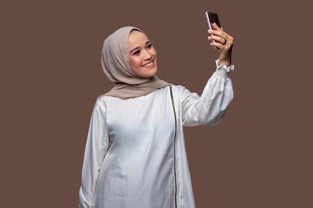 Hijab vrouw neemt een selfie met behulp van een slimme telefoon geïsoleerd op effen achtergrond