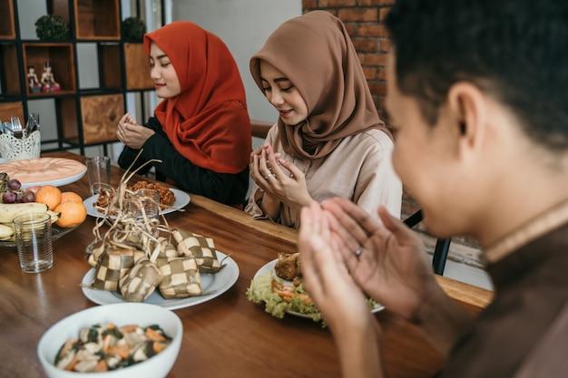 Hijab-vrouwen en een man bidden samen voor de maaltijd Premium Foto