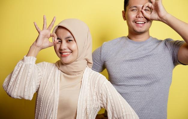 Hijab vrouwen en mannen blij en tonen samen ok teken. geïsoleerd op een gele achtergrond