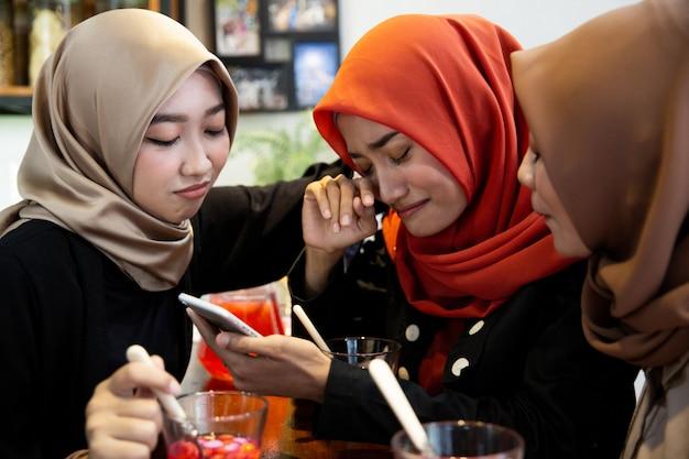 Hijab-vrouwen en vrienden verdrietig bij het lezen van slecht nieuws