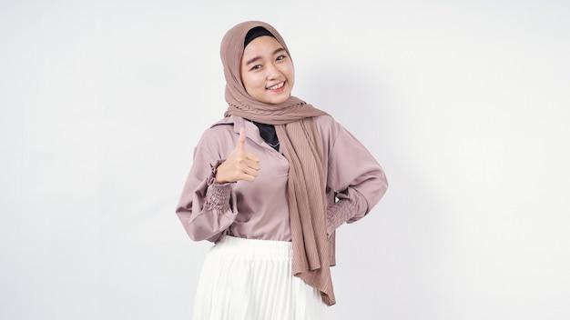 Hijabers jonge vrouw poseren glimlachend rechterhand op taille en linkerhand geven duimen omhoog geïsoleerd op witte achtergrond
