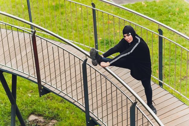 Hijabvrouw die op loopbrugbrug uitoefenen in vroege ochtend