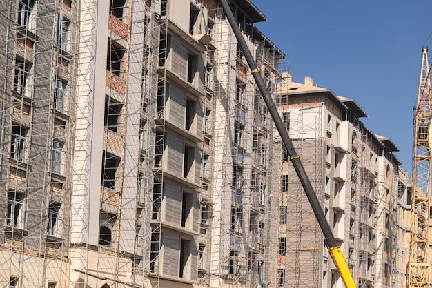 Hijsmachine op de achtergrond van het gebouw in aanbouw