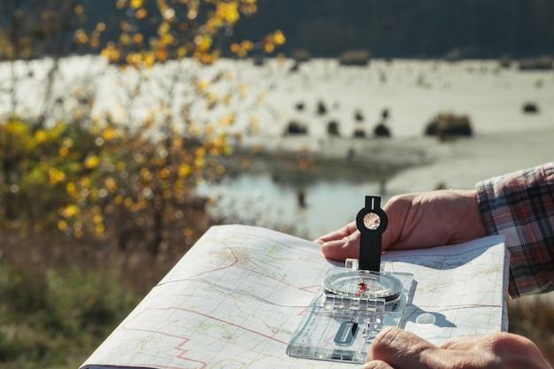 Hiking toerisme hobby close-up van man handen met kompas en kaart natuur landschap