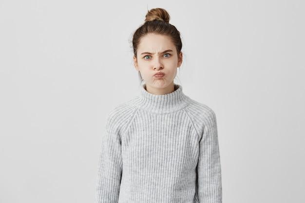Hilarisch kaukasisch meisje met trendy kapsel dat over haar wangen blaast en haar voorhoofd fronst. aanhoudende vrouw die aandacht nodig heeft, grimassend omdat ze brutaal is. emoties concept
