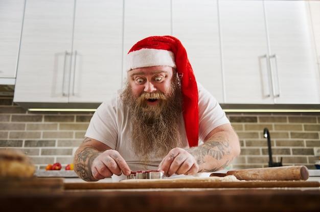 Hilarisch verrast bebaarde man in rode kerstmuts bereidt kerstkoekjes in de keuken.
