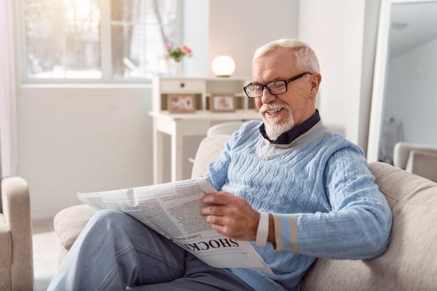 Hilarische inhoud. aangename oudere man met bril leest een artikel in de krant en glimlacht breed terwijl hij comfortabel op de bank zit