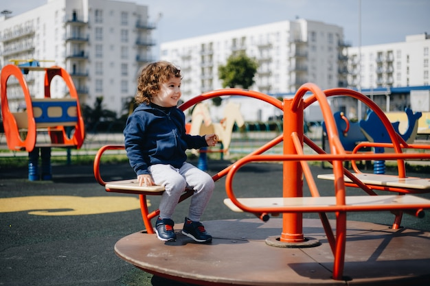 Hilarische kleine jongen in een lege speeltuin tijdens quarantaine zonder bescherming