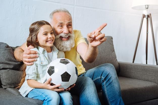 Hilarische situatie. mooi meisje houdt een bal vast en kijkt samen met haar grootvader naar een voetbalwedstrijd terwijl ze op een grappig moment met hem lacht