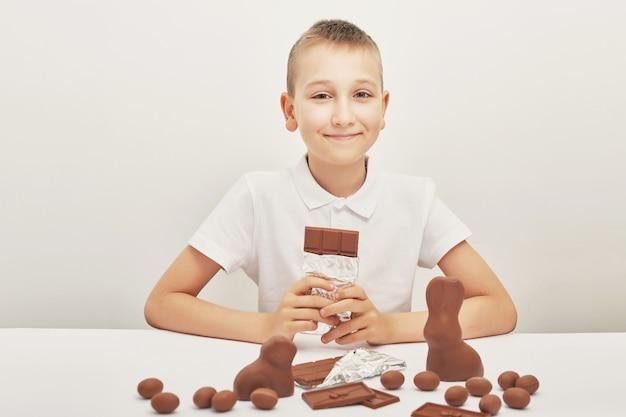 Ð¡hild jongen met chocolade konijntjes en eieren voor pasen. chocolade-eieren, konijnen en tegels. chocoladesnoepjes voor kinderen