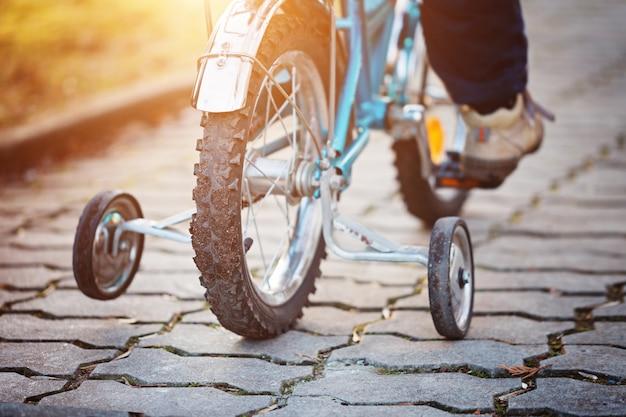 Ð¡hild op een fiets bij asfaltweg in zonnige dag. achteraanzicht