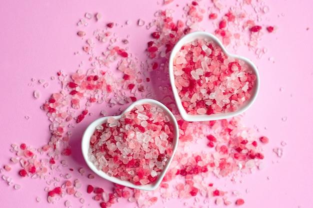 Himalaya roze zout op roze papier achtergrond in een hartvorm schotel
