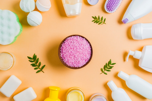 Himalayan zoute kom met cosmetische producten op gekleurde achtergrond