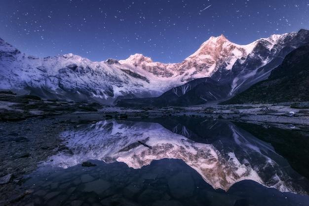 Himalaynbergen en bergmeer bij sterrige nacht in nepal