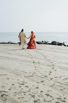 Hindoe bruidspaar loopt langs de oceaan kust