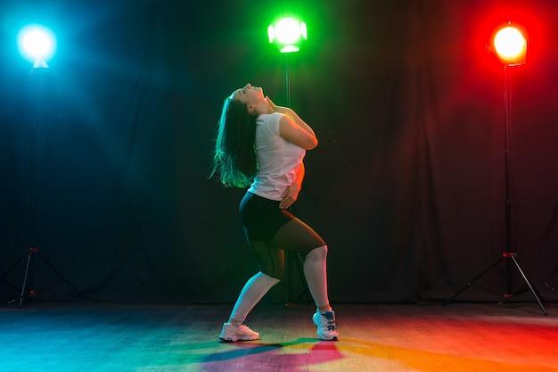 Hiphop, jazz-funk, tecktonik, waacking, trance en straatdansen concept - mooie vrouw jazz funk dansen over donkere achtergrond.