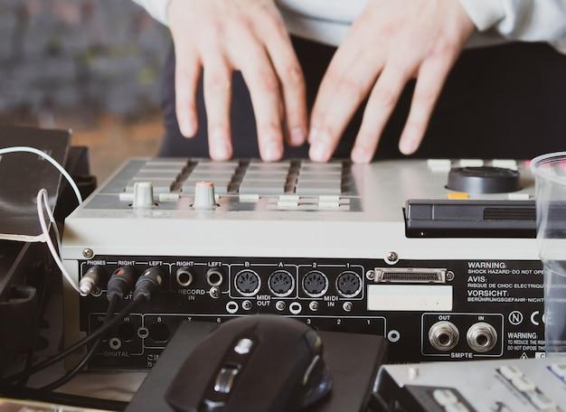 Hiphopbeats maken op een drumcomputercontroller en draaitafels in een thuisstudio