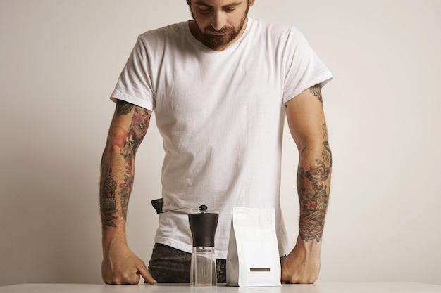 Hippe getatoeëerde barista in een effen wit t-shirt die neerkijkt op een kleine handmatige maalmachine en een witte zak met koffiebonen zonder label