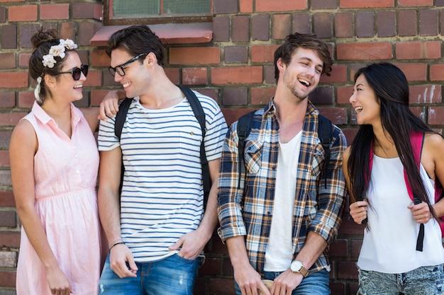 Hippe vrienden leunend tegen de muur en lachen