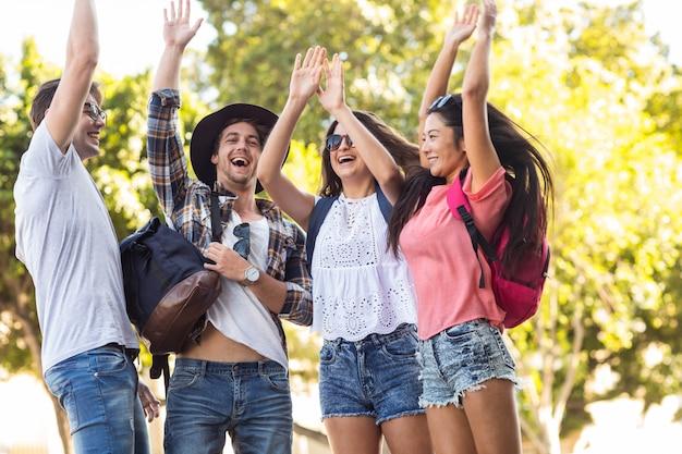 Hippe vrienden opbeuren met opgeheven armen in de straten