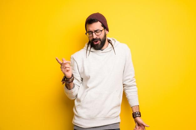 Hippie man met dreadlocks geniet van dansen tijdens het luisteren naar muziek op een feestje