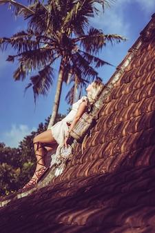 Hippie meisje met lang blond haar in een jurk op het dak.