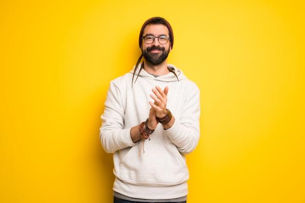 Hippiemens die met dreadlocks na presentatie in een conferentie toejuicht