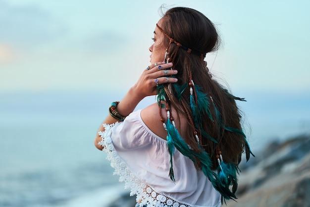 Hippievrouw die blauwe veren en juwelen en witte blouse draagt