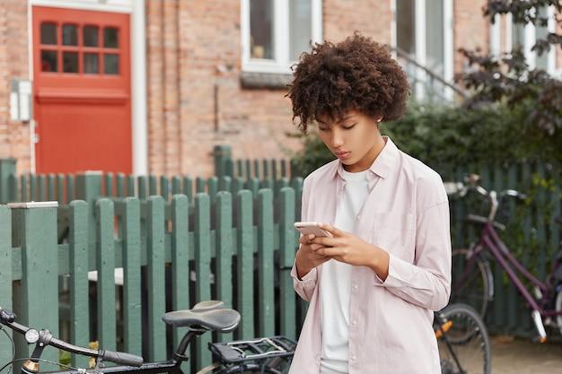 Hipster-bloger met afro-kapsel kijkt naar video op sociale netwerken, leest nieuws op de website, wandelt buiten in de buurt van een hek