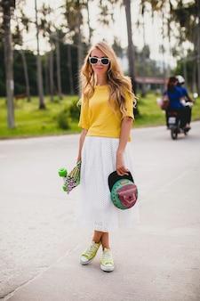 Hipster coole vrouw met skate board en pet poseren lachend op vakantie