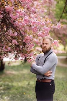 Hipster dichtbij het bloeien van sakura. harmonie met de natuur concept. man met baard en snor in de buurt van bloeiende bloemen. bebaarde man met stijlvolle kapsel met sakura bloemen
