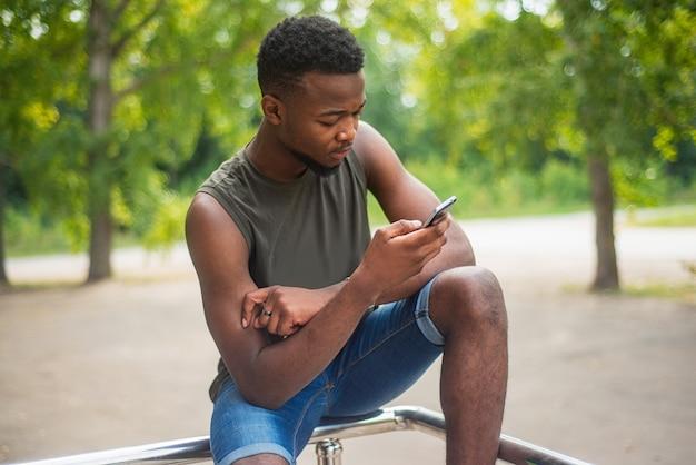 Hipster, een jonge man die een smartphone gebruikt.