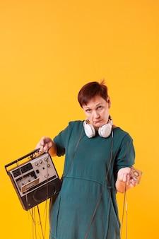 Hipster hogere vrouw die retro cassettespeler houdt