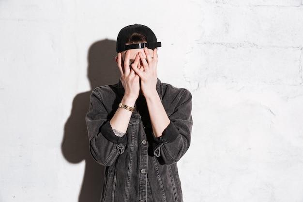 Hipster in snapback bedekt zijn gezicht