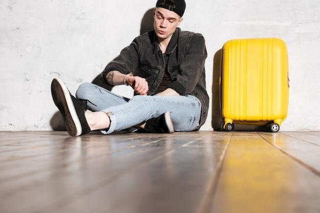 Hipster in snapback zittend op de vloer met koffer