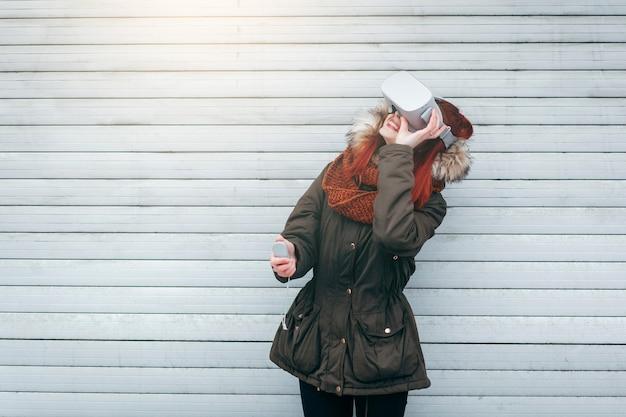 Hipster jong meisje speelt virtuele realiteit mobiele game-app op smartphone die is gekoppeld aan moderne vr-bril buiten