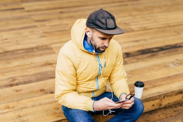 Hipster jonge bebaarde man met gele jas, stijlvolle zwarte pet en jeans zittend op houten vloer met smartphone